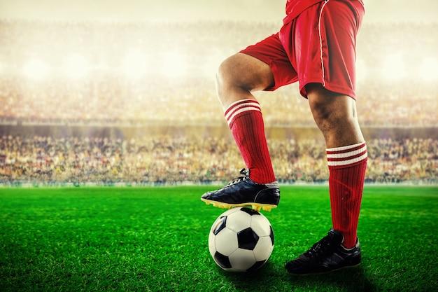 Voeten van rode teamvoetballer op voetbalbal voor start in het stadion Premium Foto