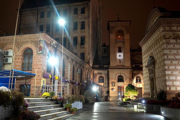 Voetstraat 's nachts met verlichting, kerk, gebouwen, groen en bloemen in boekarest, roemenië Gratis Foto