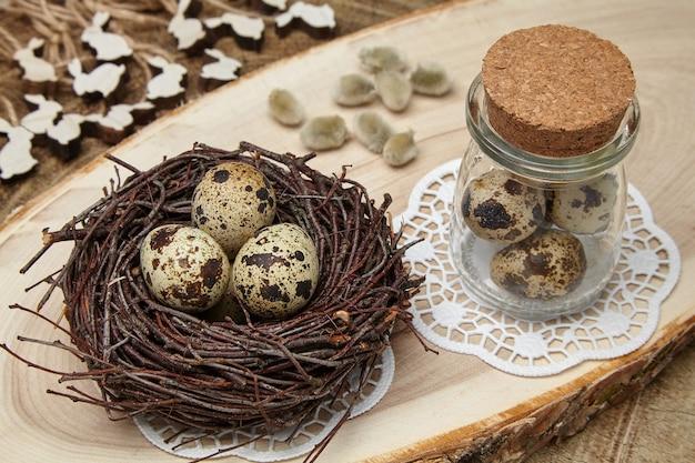 Vogeleieren in een nest, eieren in een pot, houten hazen en wilgenknoppen op een houten zaag. pasen concept Premium Foto