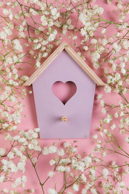 Vogelhuis zeer belangrijke die houder met de adembloem van de baby tegen roze achtergrond wordt omringd Gratis Foto