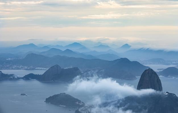 Vogelperspectief van een oceaan met bergen omgeven door wolken Gratis Foto