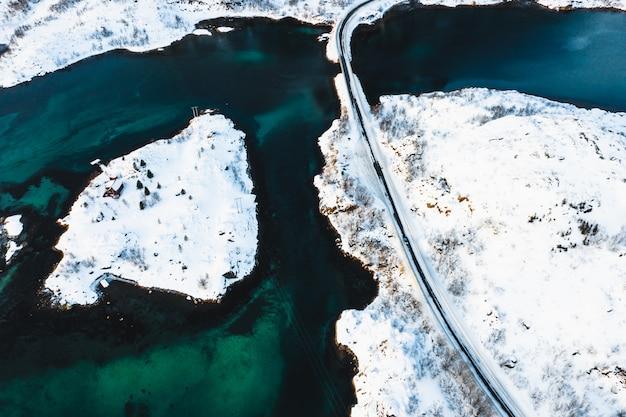 Vogelvlucht van een weg die door sneeuweilanden op een watermassa gaat Gratis Foto
