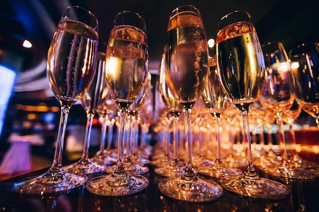 Vol glas champagne in een nachtclub. veel glazen champagne op de bar. bubbels champagne in een glas. Premium Foto