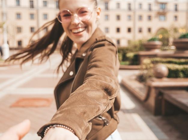 Volg mij romantisch concept jonge vrouw met lang haar buitenshuis houdt de hand van haar vriendje Gratis Foto
