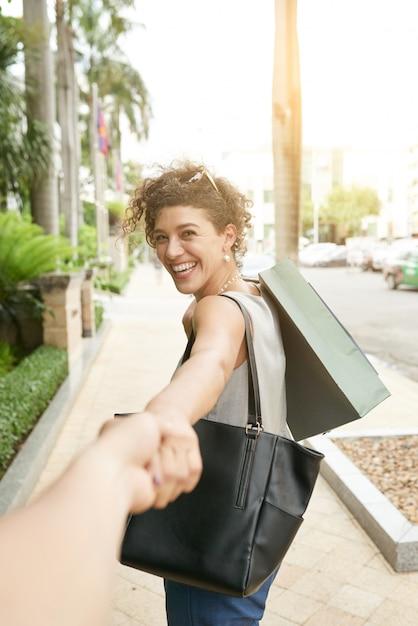 Volg mij shot van een vrouw die zich omkeert naar haar onherkenbare vrouw die haar hand vasthoudt Gratis Foto