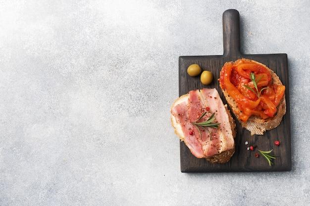 Volkoren broodsandwiches met roomkaas, bacon en ingeblikte pepers met tomaat op een houten snijplank. Premium Foto