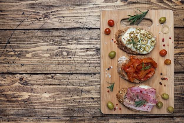 Volkoren broodsandwiches met roomkaas, bacon en olijven ingeblikte peper met tomaat op houten achtergrond. Premium Foto