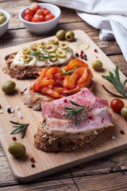 Volkoren broodsandwiches met roomkaas, spek en olijven in blik paprika met tomaat Premium Foto