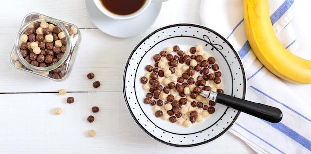 Volkoren chocolade en melk ballen, fruit, thee en melk op witte houten oppervlak. gezond ontbijtgranen. baby ontbijt. baby eten. gebalanceerd dieet. Premium Foto