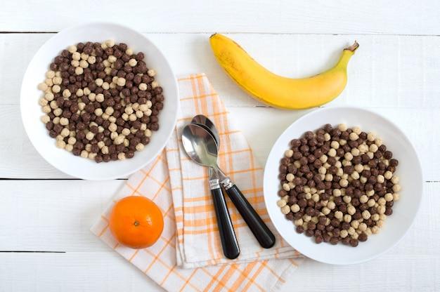 Volkoren chocolade en melk ballen in kom en fruit op witte houten oppervlak. gezond ontbijtgranen. baby ontbijt. baby eten. gebalanceerd dieet. Premium Foto
