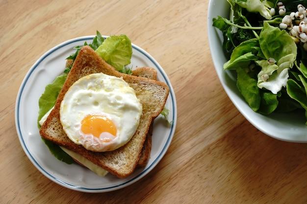 Volkoren sandwich met eieren, verse groenten, ham en kaas, gezond ontbijt voor een nieuwe dag die gelukkig en gezond is. Premium Foto