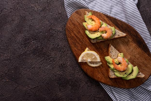 Volkoren toast sneetjes brood met guacamole, gebakken garnalen en stukjes gebakken spek op houten plank selectieve aandacht, focus op de voorkant van de garnalen op het eerste brood Premium Foto