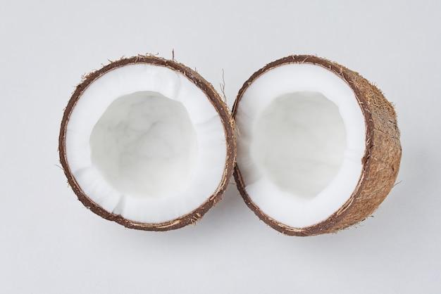 Volle kokosnoot en gebarsten half op een wit oppervlak, bovenaanzicht Premium Foto