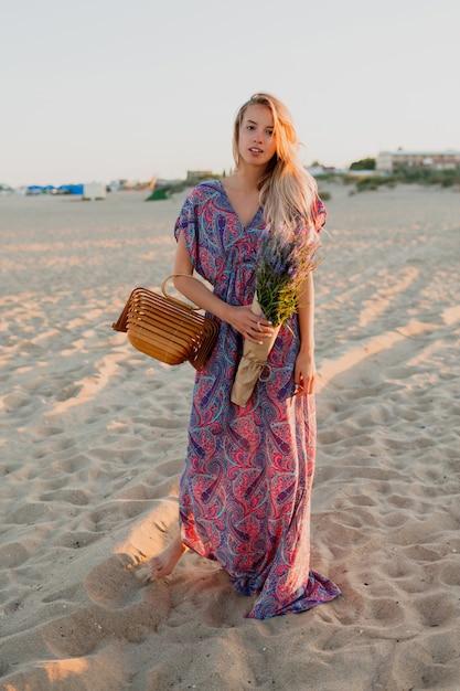 Volle lengte afbeelding van vrij blonde vrouw met boeket lavendel wandelen op het strand. sunset kleuren. Gratis Foto