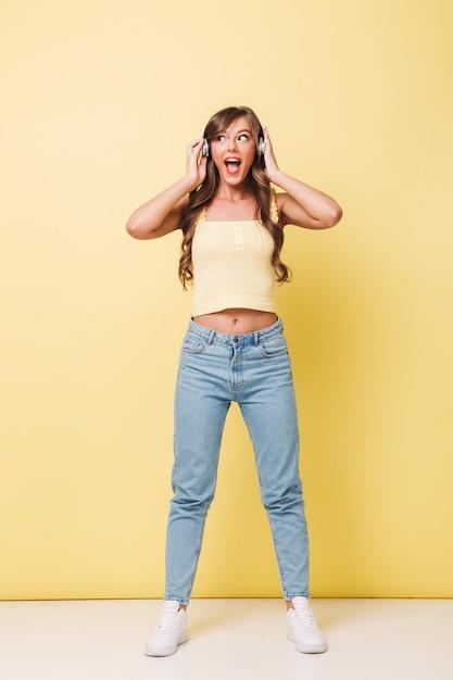 Volle lengte foto van vrolijke vrouw 20s met lang bruin haar gekleed in spijkerbroek zingend terwijl u luistert naar muziek via een koptelefoon, geïsoleerd op gele achtergrond Premium Foto