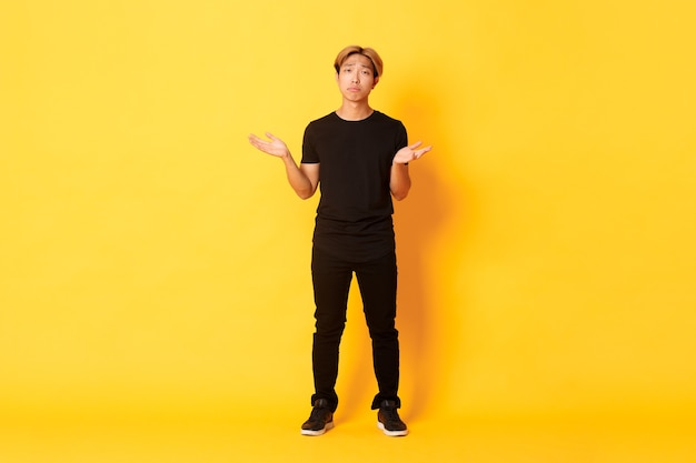 Volle lengte van teleurgestelde en gefrustreerde aziatische kerel die zijn schouders ophaalt en triest kijkt, gele muur. Gratis Foto