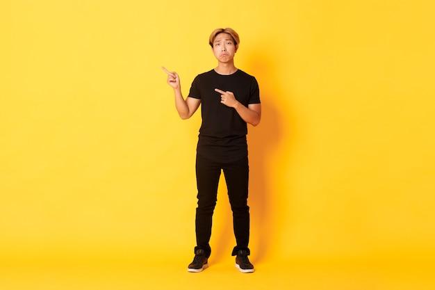 Volle lengte van trieste knappe koreaanse man met blond haar die een boos gezicht maakt, met de vingers in de linkerbovenhoek wijst, het logo met spijt toont, staande gele muur. Gratis Foto