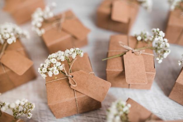 Volledig frame van kartonnen dozen met tag en baby's-adem bloemen op houten achtergrond Gratis Foto