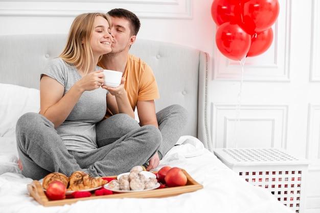Volledig geschoten gelukkig paar met ontbijt in bed Gratis Foto