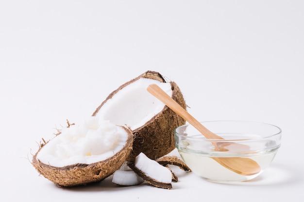 Volledig geschoten kokosnoot met kokosolie onder licht Gratis Foto