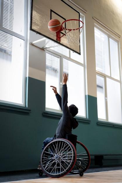 Volledig geschoten man in rolstoel basketbal spelen Gratis Foto