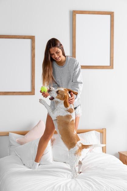 Volledig geschoten meisje in bed met puppy Premium Foto