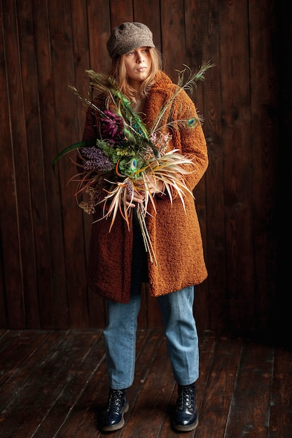 Volledig geschoten meisje met bloemen het stellen Gratis Foto