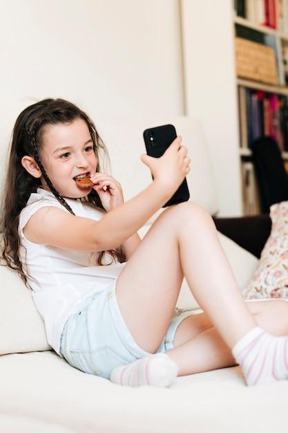 Volledig geschoten meisje met koekje dat een selfie neemt Gratis Foto