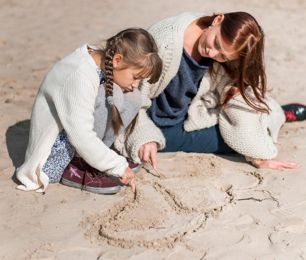 Volledig geschoten moeder en meisje die bij strand spelen Gratis Foto