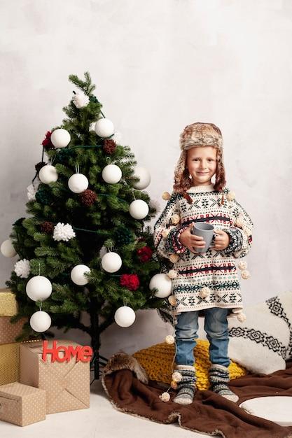 Volledig geschoten smileyjong geitje dichtbij de kerstmisboom Gratis Foto