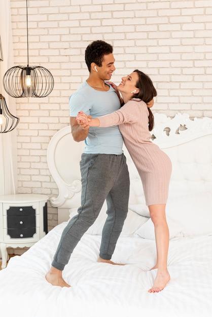 Volledig geschoten smileypaar dat aan muziek in bed luistert Gratis Foto