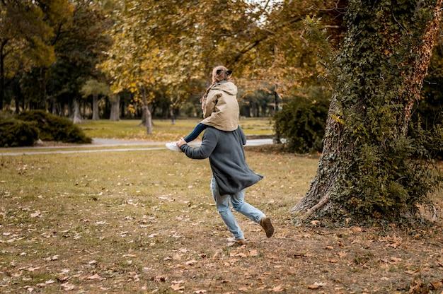 Volledig geschoten vader dragende meisje op schouders Premium Foto