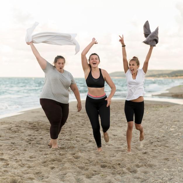 Volledig geschoten vrienden die op strand lopen Gratis Foto
