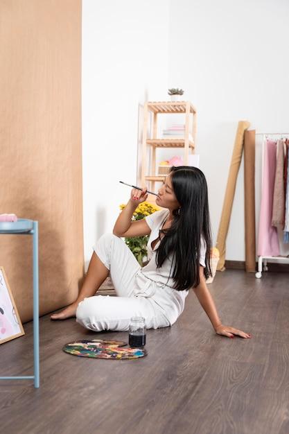 Volledig geschoten vrouw die binnenshuis creatief is Gratis Foto