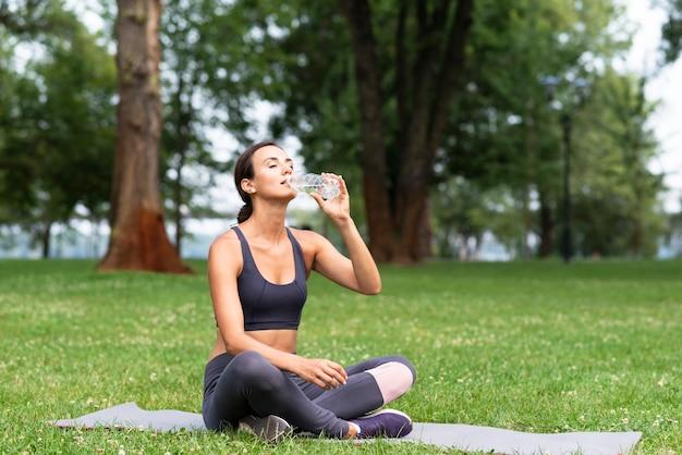Volledig geschoten vrouwen drinkwater in openlucht Gratis Foto