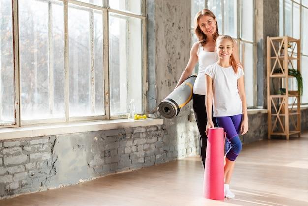 Volledig geschotene moeder en dochter die yogamatten houden Gratis Foto