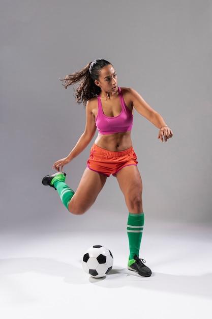Volledig geschotene voetbalvrouw het schoppen bal Gratis Foto