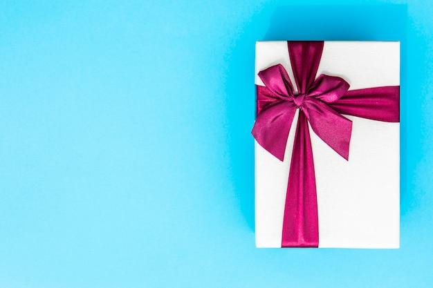 Volledig ingepakt cadeau met lint blauwe achtergrond Gratis Foto