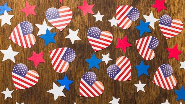 Volledig kader van de amerikaanse vlaggen en de sterren van de hartvorm op houten bureau Gratis Foto