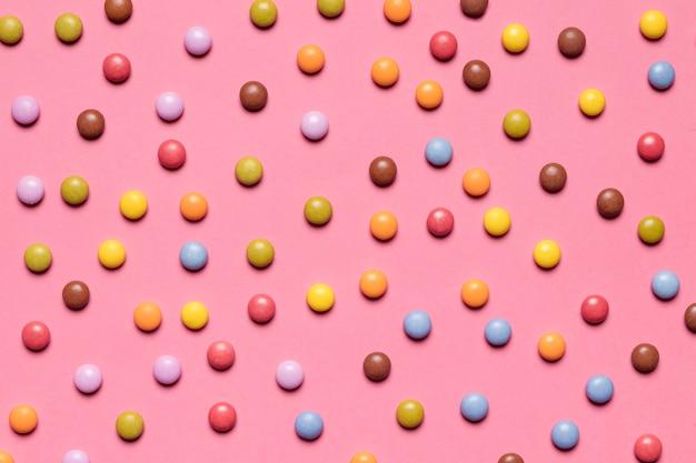 Volledig kader van kleurrijk multicolored gemsuikergoed op roze achtergrond Gratis Foto