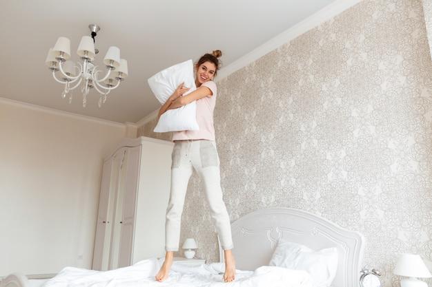 Volledig lengtebeeld van jonge vrouw die pret op bed hebben Gratis Foto