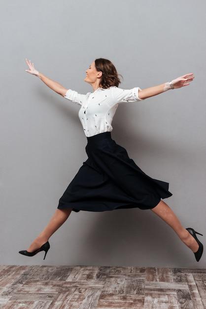 Volledig lengtebeeld van vrouw in bedrijfskleren die en in studio op grijs springen lopen Gratis Foto