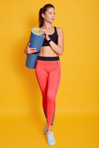 Volledig lengteportret die van mooie atletische jonge de yogamat van de vrouwenholding in handen, opzij, klaar voor het uitwerken kijken Gratis Foto