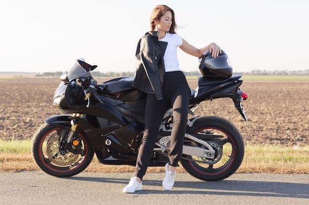 Volledig lengteportret van aantrekkelijke knappe vrouw die opzij kijkt, zich dichtbij haar voertuig bevindt, haar arm op helm zet, leerjasje, wit t-shirt, zwarte broek en witte tennisschoenen draagt. Premium Foto