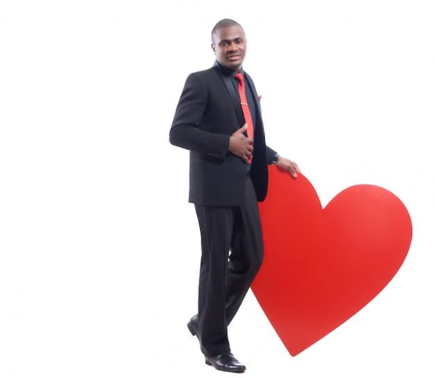 Volledig lengteportret van de jonge afrikaanse mens in zwarte reeks en rode band die op groot verfraaid rood hart leunen Gratis Foto