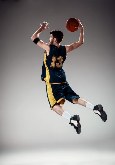 Volledig lengteportret van een basketbalspeler met bal Gratis Foto