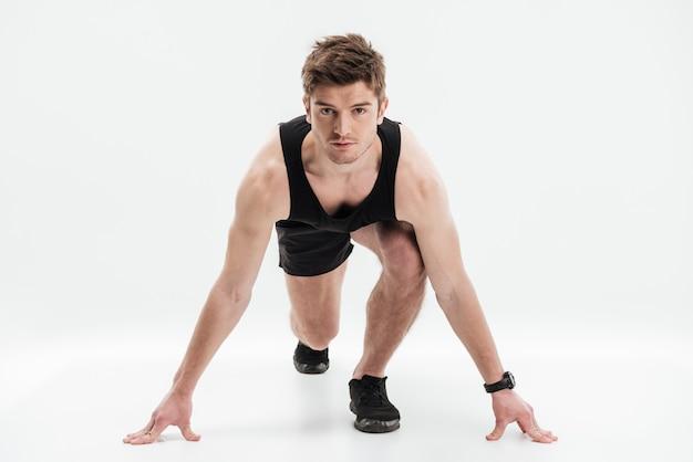 Volledig lengteportret van een geconcentreerde sportman klaar te lopen Gratis Foto