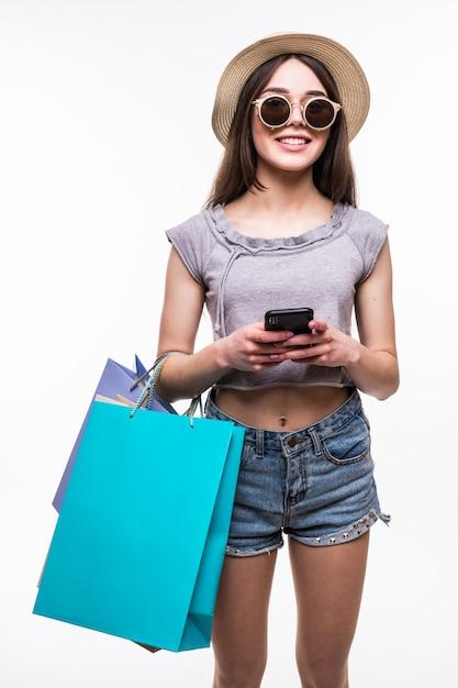 Volledig lengteportret van een gelukkige jonge geïsoleerde het winkelen zakken van de vrouwenholding en mobiele telefoon Gratis Foto