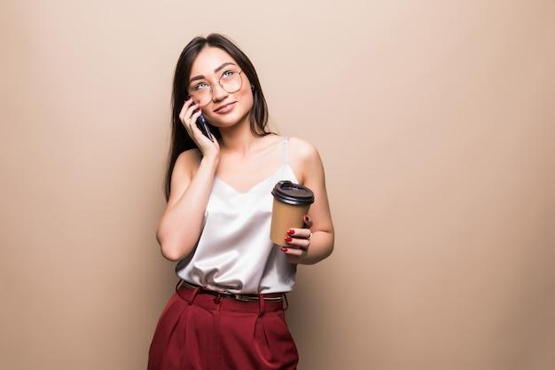 Volledig lengteportret van een glimlachende aziatische mobiele telefoon van de vrouwenbespreking terwijl het houden van kop van koffie geïsoleerd over beige muur gaan Gratis Foto