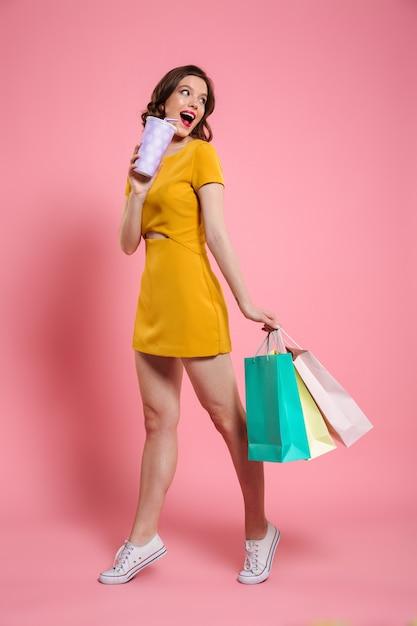 Volledig lengteportret van een glimlachende jonge vrouw in kleding Gratis Foto